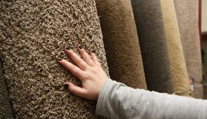 A customer feelst he fibers of a carpet roll on display at Di's Floor Centre in Springfiled, Oregon
