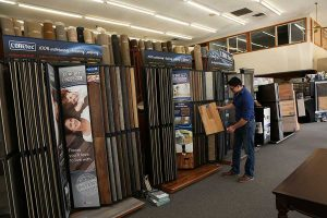 A Di's Floor Centre flooring specialist adds a new floor sample to the COREtec waterproof luxury vinyl flooring display at Di's showroom in Springfiled, Oregon